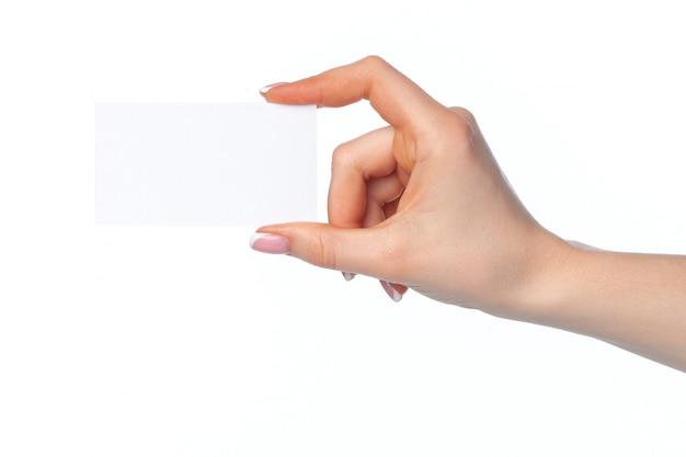 Schöne weibliche hand, die weiße visitenkarte auf weißer wand hält