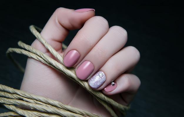 Schöne weibliche hand mit beige nageldesign.