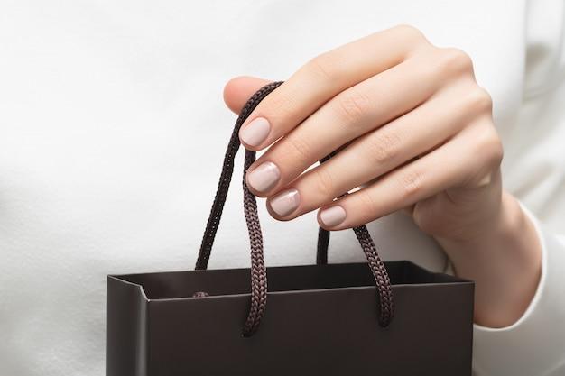 Schöne weibliche hand mit beigem nageldesign, das kleine tasche hält