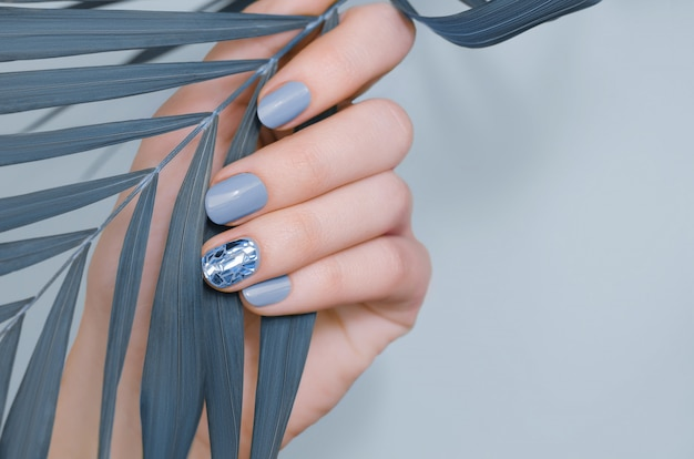 Schöne weibliche hand mit blauem nagel