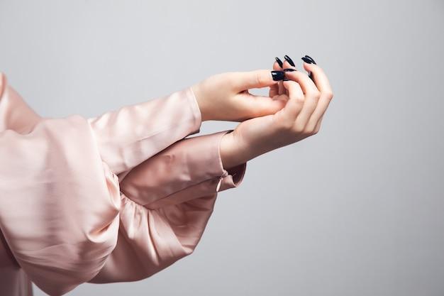 Schöne weibliche hand mit manikürenägeln auf grauem hintergrund isoliert