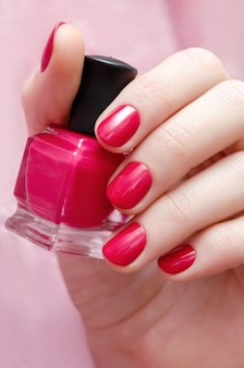 Schöne weibliche hand mit rosa nageldesign.