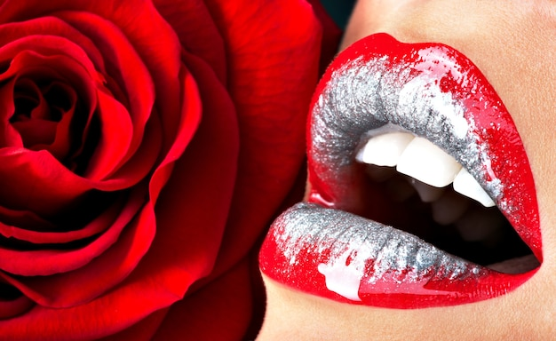 Schöne weibliche lippen der nahaufnahme mit glänzendem rotem glanzlippenstift und rose