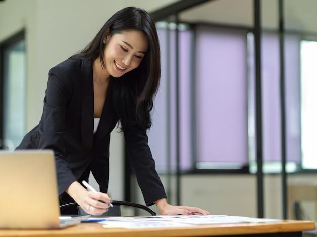 Schöne weibliche managerin steht am schreibtisch, die sich auf finanzberichte im büro konzentriert