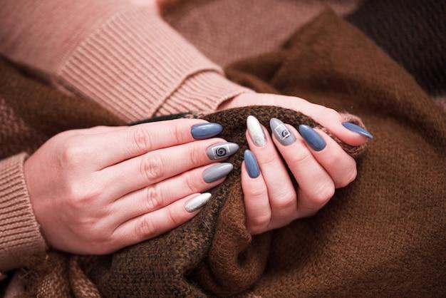 Schöne weibliche maniküre auf einer strickjackestrickjacke.