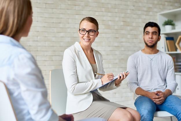 Schöne weibliche psychologin, die gruppentherapiesitzung leitet