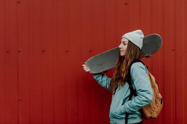 Schöne weibliche skaterin, die ihr skateboard hält