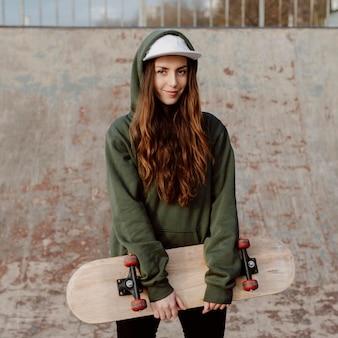 Schöne weibliche skaterin, die ihre skateboard-vorderansicht hält