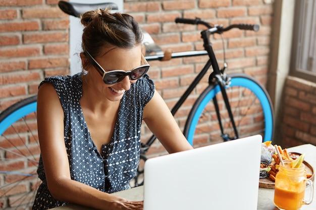Schöne weibliche tastatur auf generischem laptop-computer, die online-kommunikation genießt, während sie freunde über soziale medien mitteilt und den bildschirm mit fröhlichem lächeln betrachtet