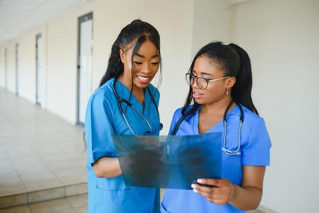 Schöne weibliche und gutaussehende afroamerikanische ärzte untersuchen röntgenfotos, zwei andere ärzte sprechen im hintergrund