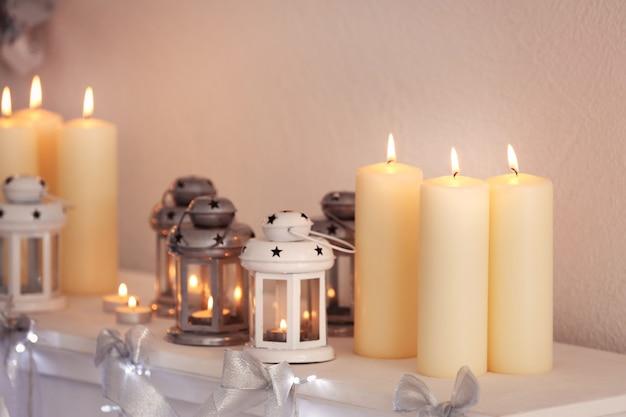 Schöne weihnachtsdekoration und kerzen auf dem kaminsims zu hause