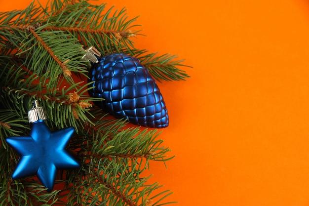 Schöne weihnachtsdekorationen auf tannenbaum auf orangem hintergrund