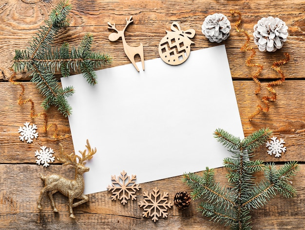 Schöne weihnachtsdekorationen mit leerer karte auf hölzernem raum
