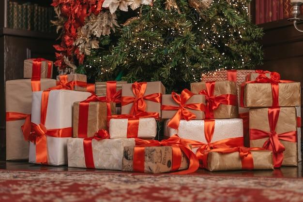 Schöne weihnachtsgeschenkboxen auf boden nahe tannenbaum im raum