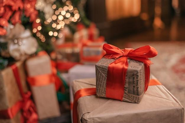 Schöne weihnachtsgeschenkboxen auf boden nahe tannenbaum im raumraum für text