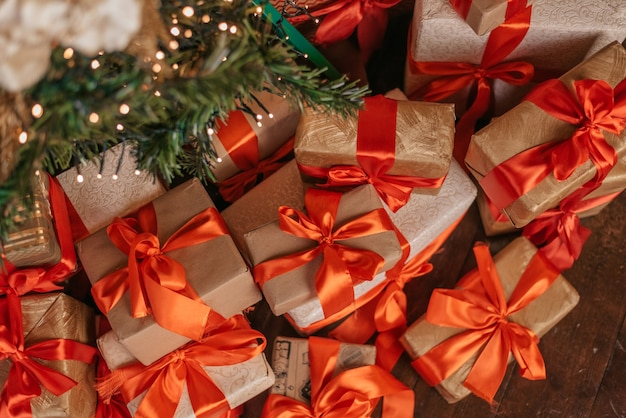 Schöne weihnachtsgeschenkboxen auf boden nahe tannenbaum in raumansicht von oben