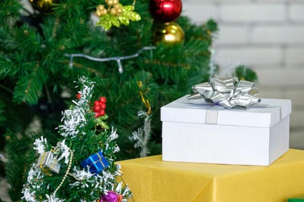 Schöne weihnachtsgeschenkboxen auf boden nahe tannenbaum