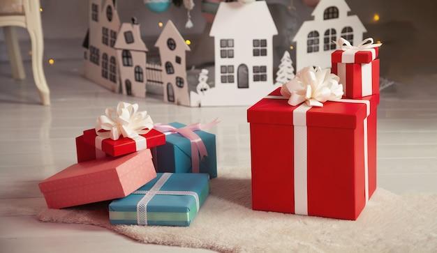 Schöne weihnachtsgeschenkboxen auf dem boden nahe dem weihnachtsbaum im raum. feiertage, geschenke, neujahr und feierkonzept - geschenkboxen auf schaffell. stapel verpackter weihnachtsgeschenke.