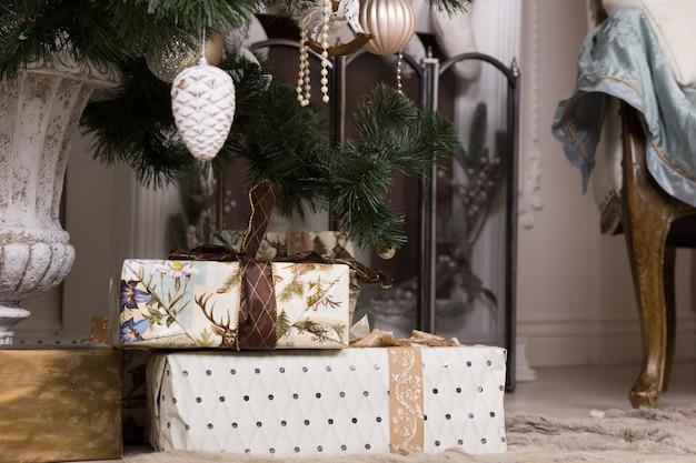 Schöne weihnachtsgeschenke unter attraktivem weihnachtsbaum mit verschiedenen dekorationen hautnah.