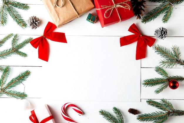 Schöne weihnachtskomposition auf weißem holzhintergrund. leere karte mit weihnachtsgeschenkboxen