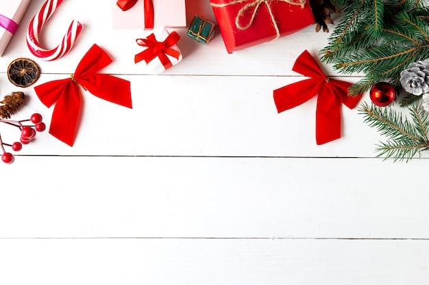 Schöne weihnachtskomposition auf weißem holzhintergrund. weihnachtsgeschenkboxen, schneebedeckte tannenzweige