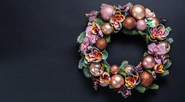 Schöne weihnachtskranzdekoration auf schwarzem. flach lag mit copyspace