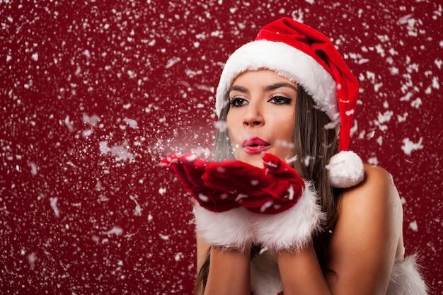 Schöne weihnachtsmannfrau, die schneeflocken bläst