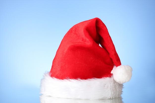 Schöne weihnachtsmütze auf blauer fläche