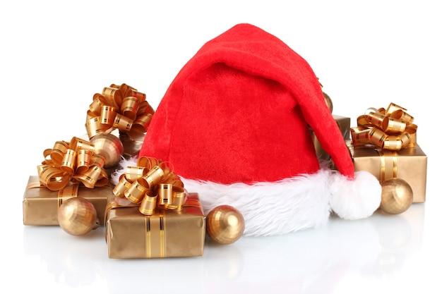 Schöne weihnachtsmütze, geschenke und weihnachtskugeln isoliert auf weiß