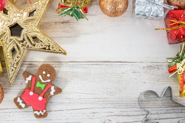 Schöne weihnachtszusammensetzung und -dekoration mit gebackenem lebkuchenmann-keks auf hellem hölzernem hintergrund