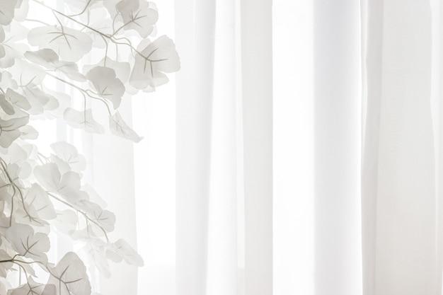 Schöne weiße blätter gegen die tüllvorhänge. hintergrund.