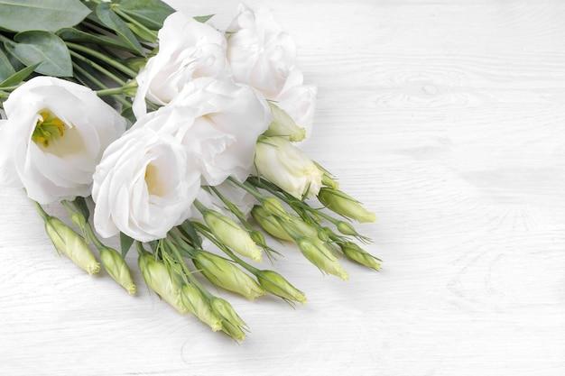 Schöne weiße blumen eustoma auf einem weißen holzhintergrund mit platz für die inschrift