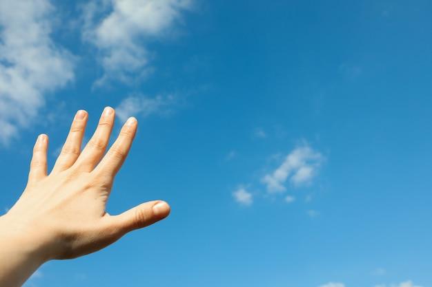 Schöne weiße flauschige wolken auf einem hellblauen himmelhintergrund mit frauenhand. wundervoller himmel
