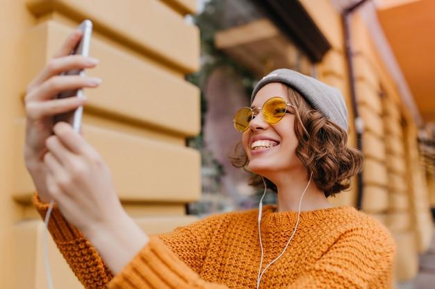 Schöne weiße frau mit lockiger frisur, die selfie im neuen outfit macht, das gutes wetter genießt