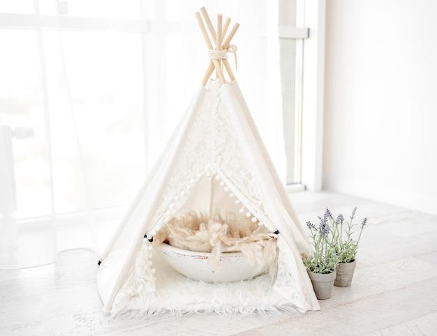 Schöne weiße hüttenhausdekoration mit becken und blumen für haustierfotosession im hellen raum. stilvolles süßes möbel wigwam für katzen-, hunde- und kaninchenstudiofotos