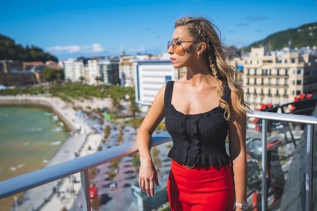 Schöne weiße kaukasische frau, die auf dem balkon des hotelzimmers mit meerblick steht