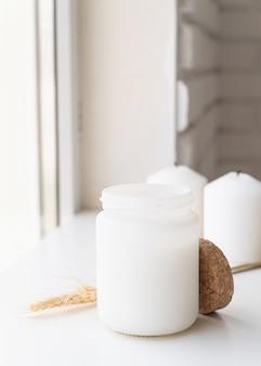 Schöne weiße kerze mit weizenspitzen auf weißer oberfläche