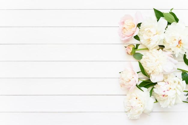 Schöne weiße pfingstrosen auf weißem hölzernem hintergrundgeburtstag valentinstag muttertag oder frauentag