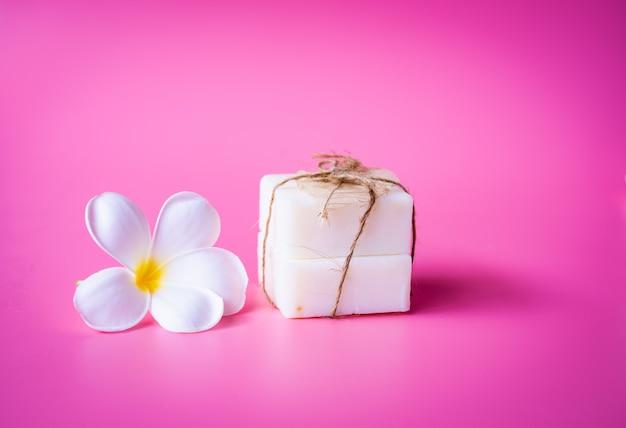 Schöne weiße plumeriablumen- und -milchseife auf rosa