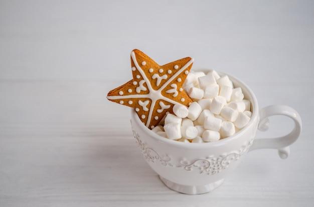 Schöne weiße tasse mit weißen marshmallows im inneren und einem lebkuchen in form eines sterns