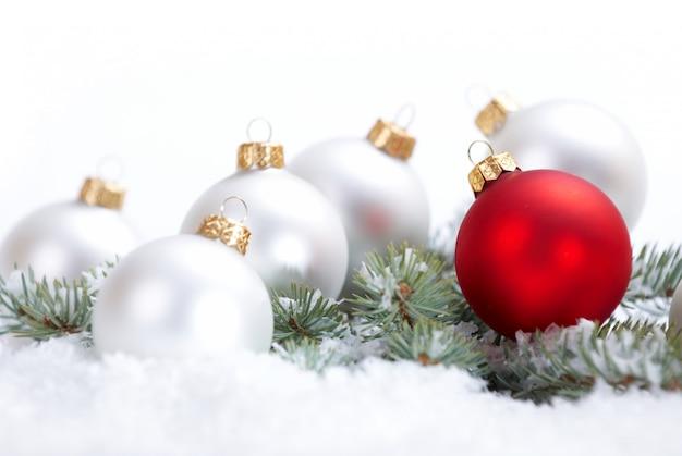 Schöne weiße und rote weihnachtskugeln mit tannenzweig und schnee auf weißem hintergrund