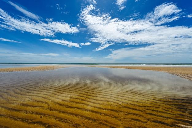 Schöne weiße wolken auf blauem himmel über ruhigem meer mit sonnenlichtreflexion