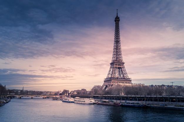 Schöne weite aufnahme des eiffelturms in paris, umgeben von wasser mit schiffen unter dem bunten himmel