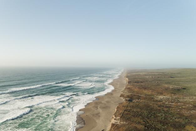 Schöne weite aufnahme des ozeans nahe einer wüste unter einem klaren blauen himmel