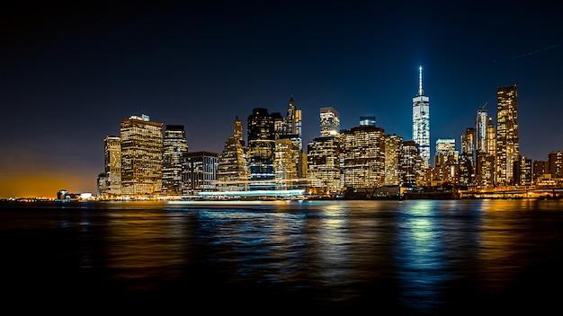 Schöne weite aufnahme einer stadtstadt bei nacht mit einem boot