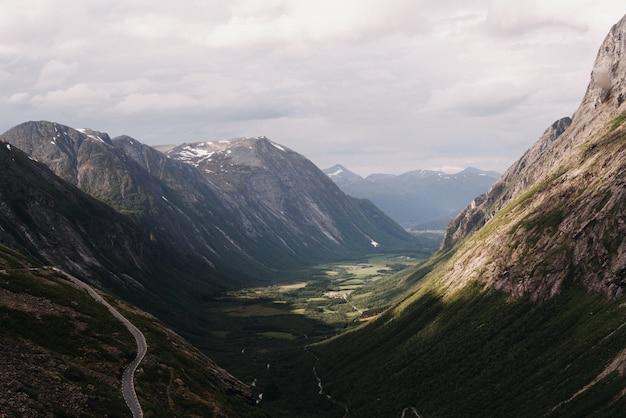 Schöne weite aufnahme von bergen, die einander gegenüberstehen, bedeckt mit grünem gras