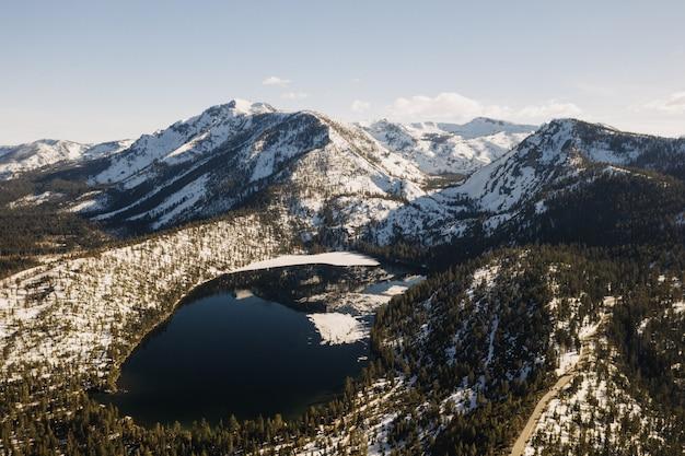 Schöne weite aufnahme von schneebedeckten bergen, umgeben von bäumen und einem see