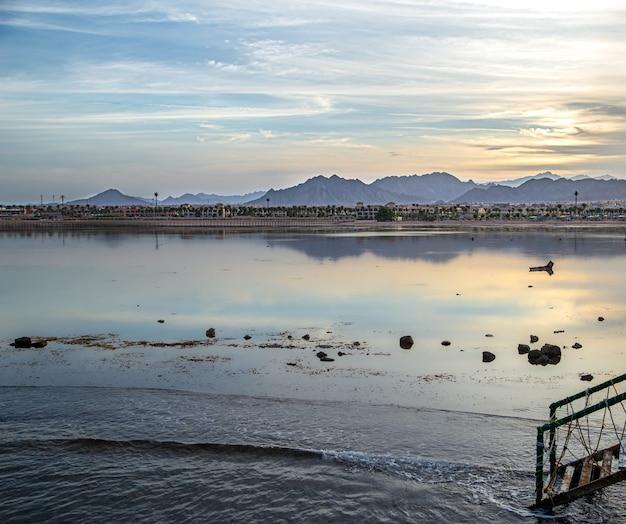 Schöne weltraumlandschaft bei sonnenuntergang am meer. mit einsamen figuren in der ferne.