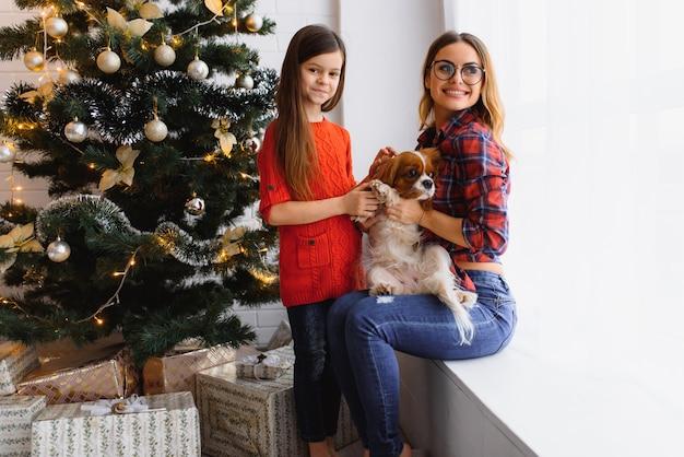 Schöne winterferien! positive brünette frau umarmt pose des kleinen mädchens mit geschenken auf dem boden im zimmer, hund nahe, haben spaß nahe weihnachtsbaum.