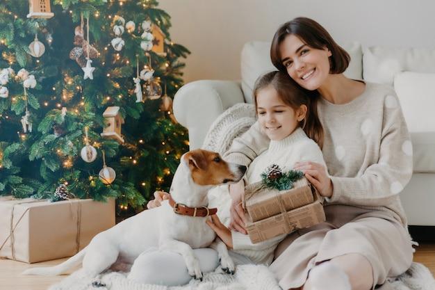 Schöne winterferien! positive brunettefrau umfasst haltung des kleinen mädchens mit geschenken auf boden im raum, jack- russellterrierhund nahe, haben spaß nahe weihnachtsbaum.